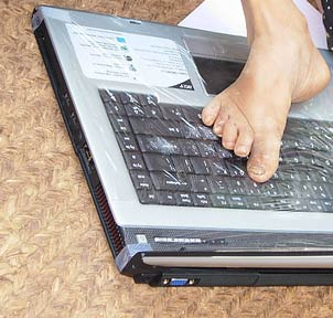 typing on laptop with foot